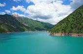 stock photo of swales  - Fascinating lake with high coast and blue sky with amazing clouds in Kyrgyzstan - JPG