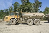 stock photo of dumper  - a yellow dirty dumper in sunny ambiance - JPG