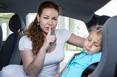 picture of shh  - Mother showing shh gesture when child asleep in car - JPG
