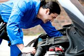stock photo of carburetor  - Smiling automobile mechanic repairing a car - JPG