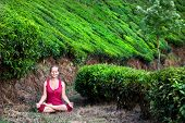 stock photo of padmasana  - Yoga meditation in padmasana lotus pose by woman in red cloth on tea plantations in Munnar hills Kerala India - JPG
