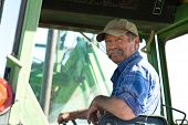 stock photo of farmer  - A candid portrait of a senior male farmer sitting in a tractor - JPG
