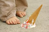 foto of upside  - a dropped rainbow colored ice cream cone lays upside down on the sidewalk at the feet of a young child - JPG