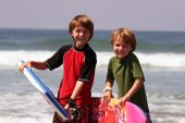 stock photo of boogie board  - Two boys at the beach holding up their Boogie Boards - JPG