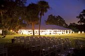 reception tent surrounded by trees, lit up at night