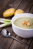 A bowl of leek and potato soup with bread croutons, over old wood table with fresh leeks and potatoe