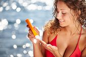 foto of sun tan lotion  - Sunscreen woman putting sunblock lotion on shoulder before tanning during summer holiday on beach vacation resort - JPG