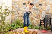 Young woman sweeping autumn leaves veranda backyard cleaning pile