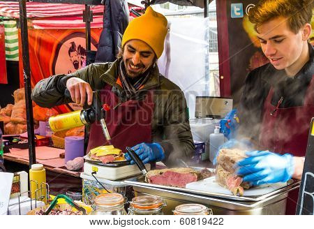 London, Uk - 1St March 2014: A Man Melting Cheese Using A Blow Torch At A Stall In Camden Food Marke