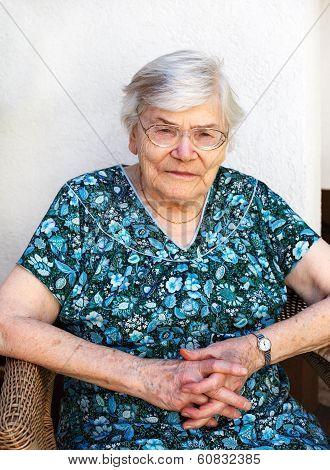 Happy Senior Woman Relaxing In Summer Garden.