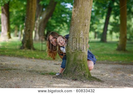 Beautiful Mother And Little Daughter Walking In Summer Park