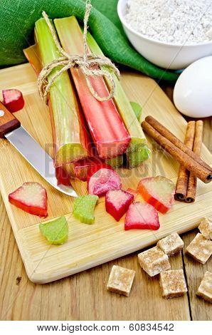 Rhubarb With Sugar And Knife On Board