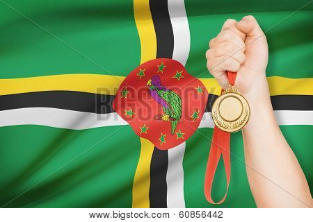 Medal In Hand With Flag On Background - Commonwealth Of Dominica