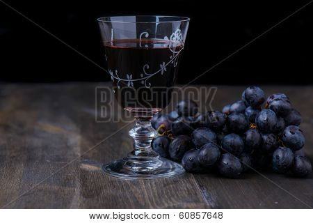 Red Wine With Grapes On The Side On Wood Table