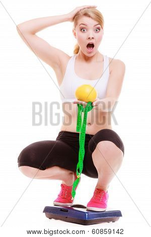 Diet Weightloss. Surprised Woman On Scale Holds Fruit Measuring Tape