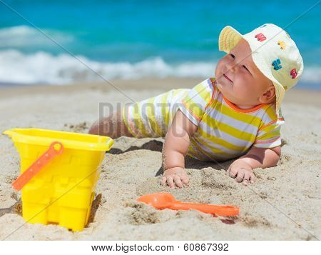 Cute baby on the tropical beach playing toys