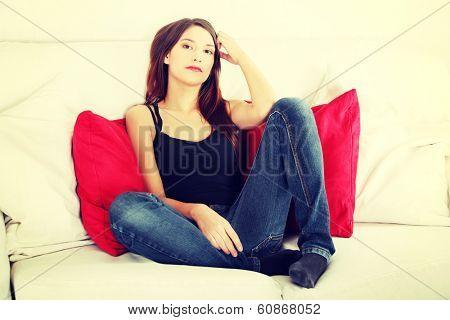 Young sad woman sitting on sofa at home