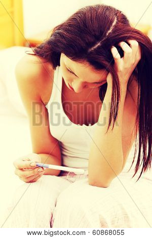 closeup of a beautiful young woman in the bedroom worrying because of the pregnancy test result.