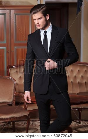 young business man standing in a vintage hotel room and unbuttoning his suit jacket while looking away from the camera