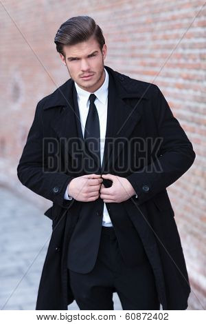 portrait of a young business man buttoning his suit outdoor while looking into the camera with a serious expression