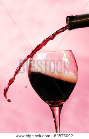 Red Wine pours into, onto, and around a wine glass filling it, spilling it and making a mess all over. Photographed with a fast shutter speed of up to 4000th of a second for beautiful stop motion.