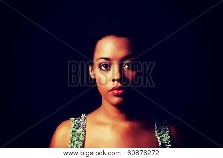 Portrait of beautiful serious afro american woman over black background