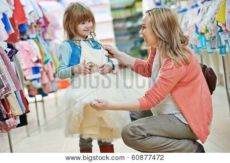 woman and little girl choosing and trying on dress clothes during shopping at garment supermarket