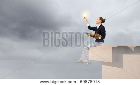 Young attractive businesswoman sitting on roof of building and reading