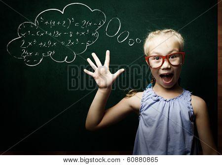 Genius girl in red glasses near blackboard with formulas