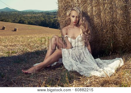 Photo of sexy blonde in a field with haystacks