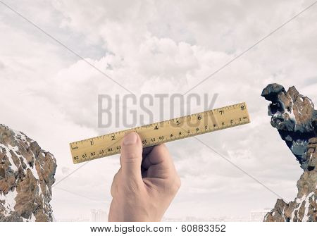 Close up of human hand measuring gap with ruler