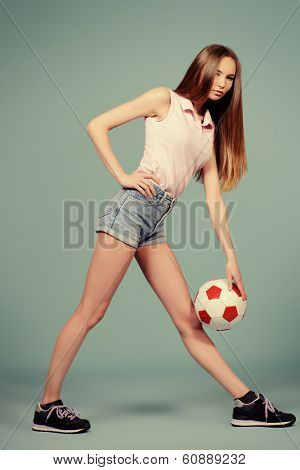 Beautiful girl teenager wearing sportive clothes posing at studio with a ball. Full length.