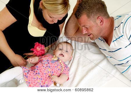 Mother and father are looking at their sweet smiling 4 month old baby.