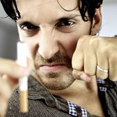 picture of stop fighting  - Angry man fighting with cigarette willing to stop smoking - JPG