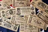 stock photo of confederation  - assorted confederate money on confederate flag background - JPG