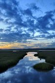 picture of inlet  - View of ocean inlet at twilight with clouds reflecting in water - JPG