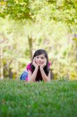 stock photo of ten years old  - Ten year old girl lying down on grass chin in hand - JPG