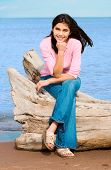 stock photo of biracial  - Beautiful biracial teen girl sitting on fallen log by lake shore in summer - JPG