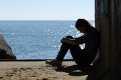 image of lonely  - Teen girl lonely and sadness on the beach with the sea in the background - JPG