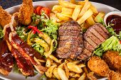 stock photo of leafy  - Wholesome platter of mixed meats including grilled steak crispy crumbed chicken and beef on a bed of fresh leafy green mixed salad served with French fries and chutney or BBQ sauce in a dish - JPG