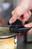 stock photo of meals wheels  - Man opening a tin of canned food using a manual can - JPG