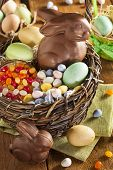 stock photo of easter candy  - Chocolate Easter Bunny in a Basket with Assorted Candy - JPG