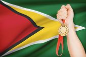 Medal In Hand With Flag On Background - Co-operative Republic Of Guyana