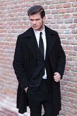 image of overcoats  - young business man posing outdoor with a hand in his pocket and the other on his overcoat while looking to his side - JPG