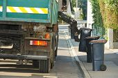 image of trash truck  - urban municipal recycling garbage collector truck loading waste and trash bin - JPG