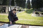 stock photo of deceased  - Woman on graveyard sitting at grave of deceased relative - JPG