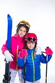 sisters kid girls with ski poles helmet and goggles going to winter snow