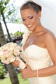 Outdoor portrait of beautiful bride with bouquet in wedding gown.