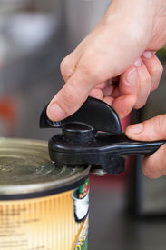 pic of tin man  - Man opening a tin of canned food using a manual can - JPG