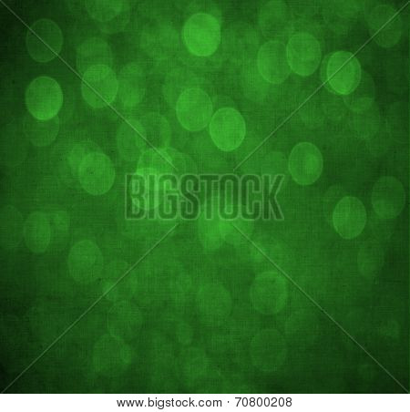 Abstract textured green or Christmas  background with bright circular shapes and a darker vignette border